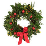 Christmas Decorative Wreath. Of holly, ivy, cedar cypress leaf sprigs and red bauble decorations with bow over white background stock image