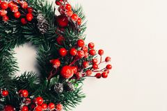 Christmas decorative wreath of holly, ivy, mistletoe, cedar and leyland leaf sprigs with red berries over white background.  royalty free stock photo