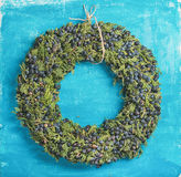 Christmas decorative wreath over bright blue painted wall background Stock Photography