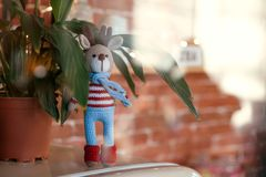 A Closed up toy amigurumi deer in striped sweater and stylish blue scarf stands near flowerpot. Free copyspace. Christmas deer. A Closed up toy amigurumi deer in stock image