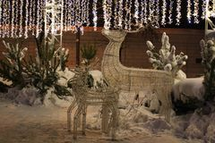 Christmas deer figures with fairy lights above royalty free stock photos