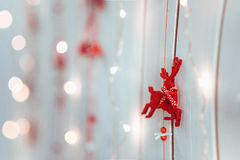 Christmas deer. Christmas and New year decoration in a shape of a red deer hanging on a white wooden texture wall among little warm lights Stock Photos