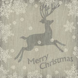 Christmas deer with snowflakes on wooden texture. Stock Image
