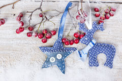 Christmas deer and stars on a branch with berries. On wooden background Stock Images