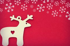 Christmas deer on textured red background of falling snowflakes, free space for text. Cute Christmas card stock photography