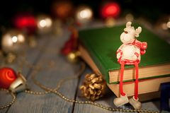 A Christmas deer toy sits on books stock photos