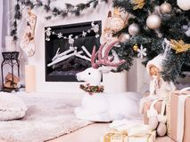 Christmas deer under New Year Tree with gifts, presents. Christmas stocking over fireplace decor, New Year`s card stock images