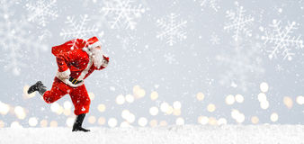 Christmas delivery rush. Santa Claus running at New Year or Christmas delivery rush with gift bag full of presents on snow Stock Images