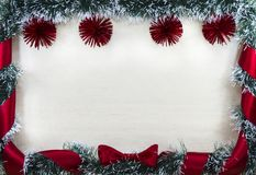 Christmas design-Christmas card bordered by pine and red balls and ribbon with bow, place for text. Studio photography royalty free stock photo
