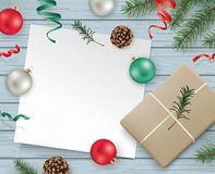 Christmas design template. Christmas flat lay design with gift box, ribbons, Christmas ornaments, pine cones, fir branches and a blank white paper on wooden Stock Photo