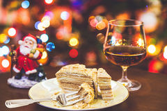 Christmas dessert. Cake on plate and glass of cognac in Royalty Free Stock Photos