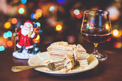 Christmas dessert. Cake on plate and glass of cognac in Royalty Free Stock Image