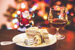 Christmas dessert. Cake on plate and glass of cognac in Stock Photo