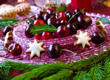 Christmas dessert - cakes with red berries cherries and cranberries. Cakes with red berries cherries and cranberries on a glass plate with christmas tweeg stock photo