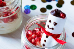 Christmas dessert with pomegranate seeds and marshmallow snowman Stock Photos