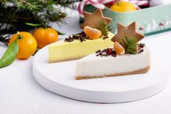Christmas Dessert Two Slice of Cheesecakes Decorated with Citrus Gingerbread Star and Berries WoodenTray White Background Fir Bran. Ches Stock Images