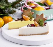 Christmas Dessert Two Slice of Cheesecakes Decorated with Citrus Gingerbread Star and Berries WoodenTray White Background Fir Bran. Ches Citrus stock photo