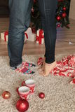 Christmas details. legs of couple on beige carpet Royalty Free Stock Photo