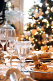 Christmas dining table. A decorated christmas dining table with wine glasses and christmas tree in background Stock Images