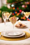 Christmas dining table. Decorated christmas dining table with champagne glasses and christmas tree in background Stock Photography