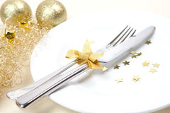 Christmas dinner. Christmas table with cutlery and golden ribbon Stock Photos
