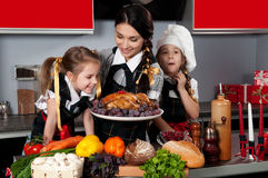Christmas Dinner. Mother with two daughters in the kitchen preparing Christmas dinner with turkey and vegetables Stock Photo
