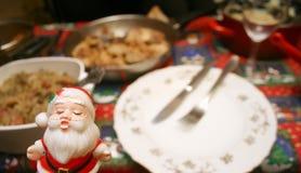 Christmas dinner. Kissing santa doll in front of christmas dinner Royalty Free Stock Images