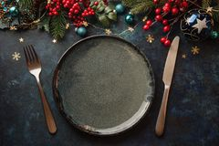 Christmas dinner plate. Christmas dinner background, plate and decor on dark rustic table, top view royalty free stock image