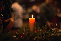 Christmas dinner with a burning candle in the middle and bokeh. Dark image of a magical celebration with soft light and blurred background. Some space for text royalty free stock photography