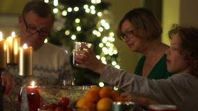 Christmas dinner by candlelight. The boy holds out a glass and he is poured a red compote from a jug. Happy family. Christmas holidays stock video