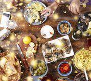 Christmas dinner. Falling golden snowflakes. Cheers Top of view of a nicely served wooden table Christmas dinner with tasty dishes. Christmas dinner. Cheers Stock Images