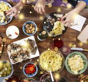 Christmas dinner. Falling golden snowflakes. Cheers Top of view of a nicely served wooden table Christmas dinner with tasty dishes. Christmas dinner. Cheers Top Royalty Free Stock Image