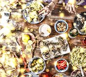 Christmas dinner. Falling golden snowflakes. Cheers Top of view of a nicely served wooden table Christmas dinner with tasty dishes. Christmas dinner. Cheers Top Royalty Free Stock Images