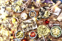 Christmas dinner. Falling golden snowflakes. Cheers Top of view of a nicely served wooden table Christmas dinner with tasty dishes. Christmas dinner. Cheers Top Stock Images
