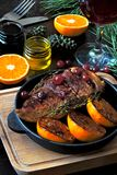 Christmas dinner. Chicken breast baked with tangerines and cranberries. Christmas tree branches and a glass of wine. Christmas moo stock photo