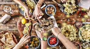 Christmas dinner. Falling golden snowflakes. Cheers Top of view of a nicely served wooden table Christmas dinner with tasty dishe. Falling golden snowflakes Royalty Free Stock Images