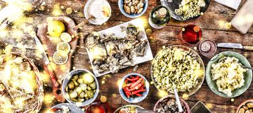 Christmas dinner. Falling golden snowflakes. Cheers Top of view of a nicely served wooden table Christmas dinner with tasty dishes. Christmas dinner. Cheers Top Stock Photography