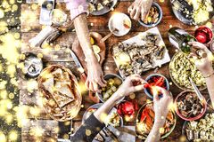 Christmas dinner. Falling golden snowflakes. Cheers Top of view of a nicely served wooden table Christmas dinner with tasty dishes royalty free stock images