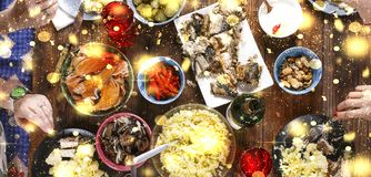 Christmas dinner. Falling golden snowflakes. Cheers Top of view of a nicely served wooden table Christmas dinner with tasty dishes. Christmas dinner. Cheers Top Royalty Free Stock Photography