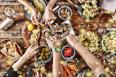 Christmas dinner. Falling golden snowflakes. Cheers Top of view of a nicely served wooden table Christmas dinner with tasty dishe. S and snacks, friends are Stock Images
