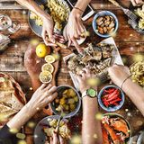 Christmas dinner. Falling golden snowflakes. Cheers Top of view of a nicely served wooden table Christmas dinner with tasty dishe. Christmas dinner. Cheers Stock Photo