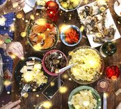 Christmas dinner. Falling golden snowflakes. Cheers Top of view of a nicely served wooden table Christmas dinner with tasty dishes. Falling golden snowflakes Stock Images