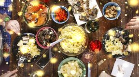 Christmas dinner. Falling golden snowflakes. Cheers Top of view of a nicely served wooden table Christmas dinner with tasty dishes. And snacks, friends are Stock Images