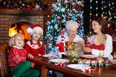 Christmas dinner. Family with kids at Xmas tree. Royalty Free Stock Photography