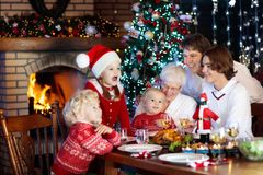 Christmas dinner. Family with kids at Xmas tree. Family with children eating Christmas dinner at fireplace and decorated Xmas tree. Parents and kids enjoy Stock Image