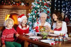 Christmas dinner. Family with kids at Xmas tree. Royalty Free Stock Image