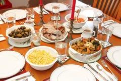 Christmas Dinner. Festive dinner table set with dinnerware and bowls Christmas holiday favorite foods of fruit stuffed pork tenderloin, corn, herb vegetable Royalty Free Stock Photography