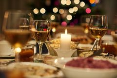 Christmas dinner fiesta. Beautiful dining table full of a variety of delicious festive food and wine with a Christmas tree in the background in candle ight mood Stock Image