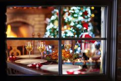 Christmas dinner at fire place and Xmas tree. Christmas dinner at fireplace and decorated Xmas tree. Dish with roasted turkey, salad and baked potato served for stock images