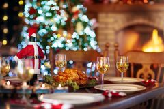 Christmas dinner at fire place and Xmas tree. Christmas dinner at fireplace and decorated Xmas tree. Dish with roasted turkey, salad and baked potato served for Stock Image